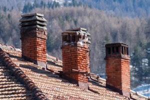 three old damaged chimneys made of bricks