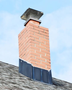 masonry chimney with black flashing and a chimney cap