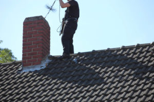 chimney sweep cleaning out chimney