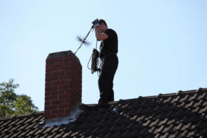 sweep on roof inspecting chimney